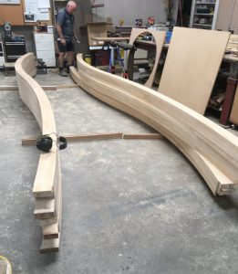 Man working on the curved wood beams inside the warehouse