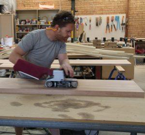 Man laminating the wood beam